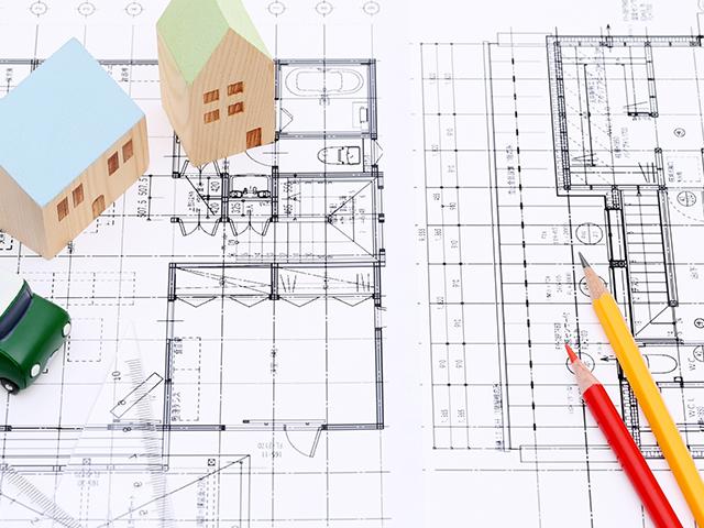 建築図面の上に家、車の模型と鉛筆、色鉛筆が