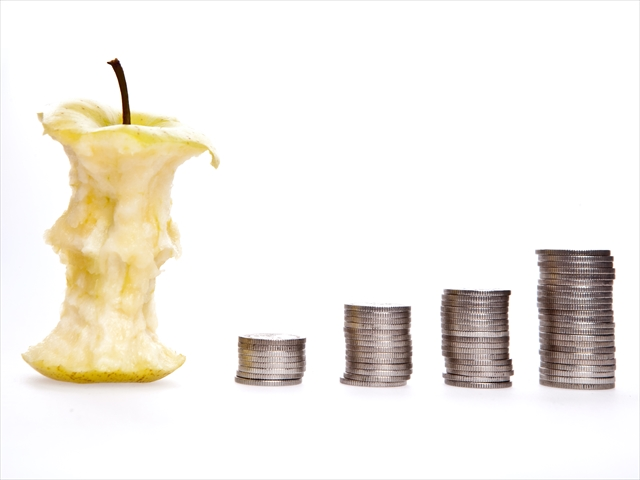 食べかけのリンゴの横にコインが階段状に並んでいる