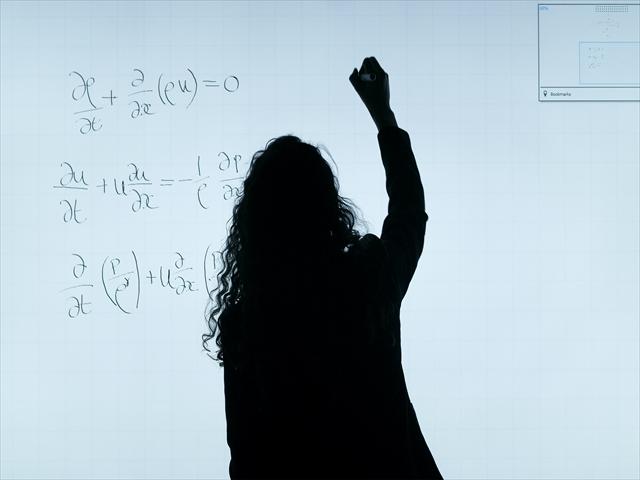 ホワイトボードに数式を書いている女性