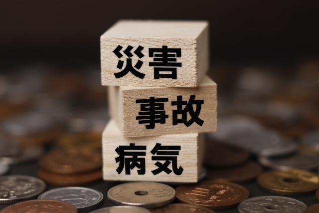 硬貨の上に災害、事故、病気とペンで書かれた木片