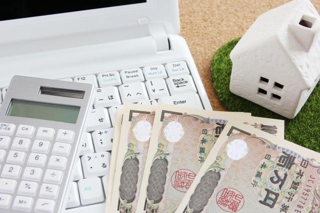 PCの上にある電卓と1万円札