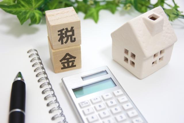 ノートの上にある電卓と家の模型と税金を書かれたキューブが二つ