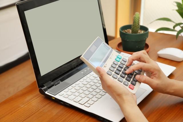 パソコンの前で電卓を打つ女性